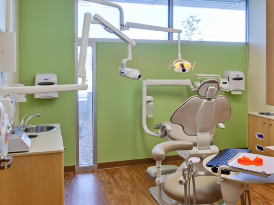 Dental operatory with backlit image and clear story glazing for positive distractions and daylighting in every operatory.